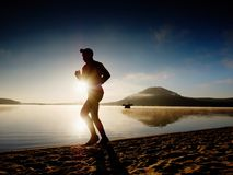 Tall fit man running along the sea shore in morning. Healthy male jogging on beach. Tall fit man running along the sea shore in morning. Healthy male jogging on Stock Photo