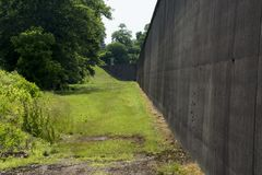 Flood wall protection. A tall Flood wall with grass border protects a community from high water when the river behind the wall rises stock photo
