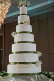 Tall  flowers next to a wedding cake. Stock Photography