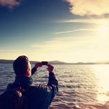 Tall ginger hair man tourist taking photos or video with phone. Autumn sunny day at sea Royalty Free Stock Photography