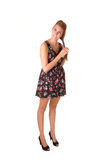 Tall girl. A young tall woman standing in the studio, playing with her hair, in heels and a short dress, for white background stock photography