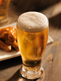 Tall glass of beer with foamy head. Close up photo shot with selective focus of a tall glass of beer with foamy head Royalty Free Stock Photography