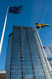 Tall glass building. Office skyscraper towards a clouded sky. Glass building with Swedish and EU banner royalty free stock image