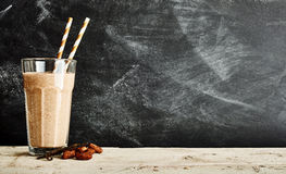 Tall glass of chocolate smoothie on a long table Royalty Free Stock Images