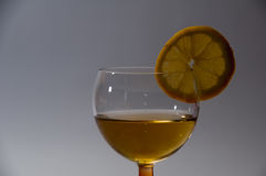 A tall glass of cocktail with lemon in a dark environment Stock Photos