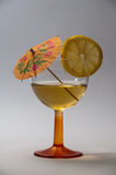 A tall glass of cocktail with lemon and umbrella in a dark envir Royalty Free Stock Images