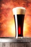 Tall glass of dark beer with foam and wooden Stock Photo