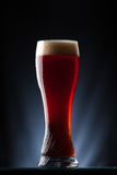 Tall glass of dark beer over a dark background Stock Photo