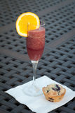 Tall glass of fresh blueberry smoothie next to blu. Tall glass of fresh blueberry orange smoothie with a homemade blueberry muffin Stock Images