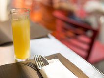 Tall glass of juice on an outdoor cafe table, with cutlery wrapped ready for a meal Royalty Free Stock Images