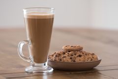 A Tall Glass Of Latte and some Cookies. A tall glass of caffe latte and some chocolate chip cookies on a round plate all placed on a oak wooden table Royalty Free Stock Photos