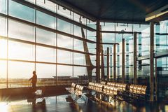 Airport terminal with silhouette of male tourist. Tall glass and metal waiting hall of modern railway station depot or airport terminal with silhouette of man Royalty Free Stock Image