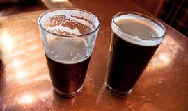 2 tall glasses of dark beer on a copper top table royalty free stock images