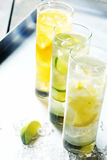 Tall glasses of iced citrus drinks for summer. Served on ice with fresh sliced fruit for a quenching beverage royalty free stock photography