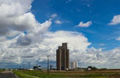 Tall grain elevators in the midwestern United States sorrounded by trucks and equipment and powerlines beside a highway all under stock images