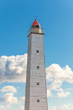 Tall gray lighthouse tower with red light Stock Images