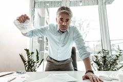 Tall grey-haired adult manager in eyeglasses clutching the paper in his hand. Boss in anger. Tall grey-haired adult manager wearing eyeglasses clutching the royalty free stock photos