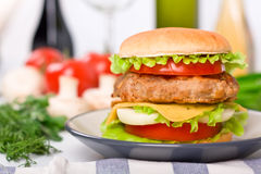 Tall hamburger on a plate Royalty Free Stock Photos