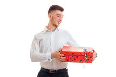 Tall handsome guy in a shirt holding a great gift. Isolated on white background Royalty Free Stock Image