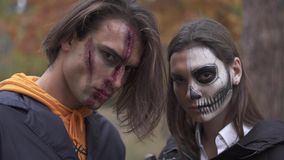 Tall handsome man with big wound on his face and pretty girl with skull makeup standing near, both looking in camera. With evil faces showing cleavers. People stock footage