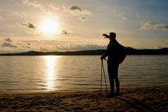 Tall hiker in dark sportswear with poles and sporty backpack on beach enjoy sunset at horizon. Magic autumn day. Royalty Free Stock Image