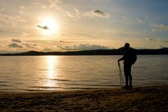 Tall hiker in dark sportswear with poles and sporty backpack on beach enjoy sunset at horizon. Magic autumn day. Stock Images
