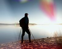 Tall hiker in dark sportswear with poles and sporty backpack walk on beach. Tourist enjoy sunrise Stock Photos