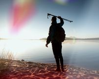 Tall hiker in dark sportswear with poles and sporty backpack walk on beach. Tourist enjoy sunrise Stock Photography