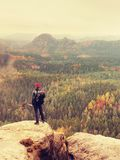 Tall hiker man with red cap,  poles in hand and with big backpack stand on rock. Misty spring Stock Image