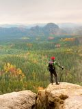 Tall hiker man with red cap,  poles in hand and with big backpack stand on rock. Misty spring Royalty Free Stock Photos
