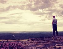 Tall hiker or sportsman on the cliff in rocky mountains park and watch down landscape Royalty Free Stock Photo