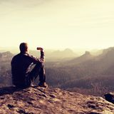 Tall hiker is taking photo by smart phone on the peak of mountain  at sunrise. Royalty Free Stock Images