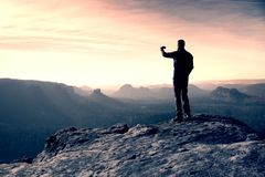 Tall hiker is taking photo by smart phone on the peak of mountain  at sunrise. Royalty Free Stock Photo