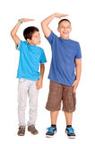 Tall. Little boys trying to be taller isolated in white Stock Photo
