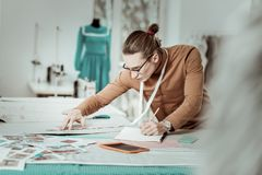 Tall long-haired young designer from a fashion school in eyeglasses looking busy. Time for work. Tall long-haired young designer from a fashion school in royalty free stock photo