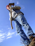 Tall Lumberjack Man. Large man with axe against a blue sky Stock Image