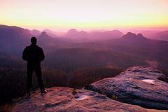 Tall man in black on cliff and watch to mountain sunrise.Silhouette in selfconfident pose Stock Photography
