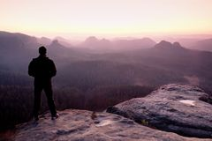 Tall man in black on cliff and watch to mountain sunrise.Silhouette in selfconfident pose. Dark silhouette of rocks royalty free stock photography