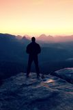 Tall man in black on cliff and watch to mountain sunrise.Silhouette in selfconfident pose. Dark silhouette of rocks royalty free stock photo