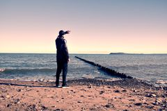 Tall man in black suit exercising and make stretching on stony beach at breakwater. Stock Photos