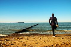 Tall man in black suit exercising on stony beach at breakwater. Stock Photography