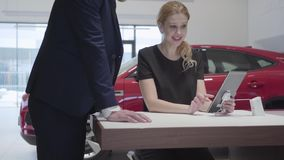 Tall man comes to confident seller woman sitting at the table. Woman shows information to man customer on tablet in. Tall man comes to confident seller woman stock video footage