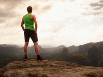 Tall man enjoy freedom on peak of mountain edge. Alone tourist  watching over misty valley. To Sun. Beautiful moment in nature.  Short hair man in black pants Stock Image