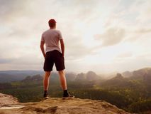 Tall man enjoy freedom on peak of mountain edge. Alone tourist  watching over misty valley. To Sun. Beautiful moment in nature.  Short hair man in black pants Royalty Free Stock Images