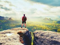 Tall man enjoy freedom on peak of mountain edge. Alone tourist  watching over misty valley. To Sun. Beautiful moment in nature.  Short hair man in black pants Stock Images