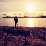 Tall man goes to lake coast near old wooden empty bench. Vintage toned photo Stock Photos