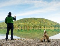 Tall man hold phone, take selfie at autumn mountain lake scenery. Vivid and vignetting effect. Poor lighting condition. Tall man hold cellphone, take selfie at stock photos