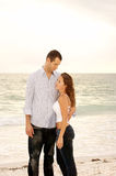 Tall man holding shorter woman. Tall handsome man looking down at shorter woman  and holding her close at the beach with ocean waves in the background Royalty Free Stock Image