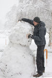 Tall man making really tall snowman Royalty Free Stock Photo