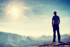 Tall man in outdoor clothes stands alone on the peak of rock. royalty free stock photography
